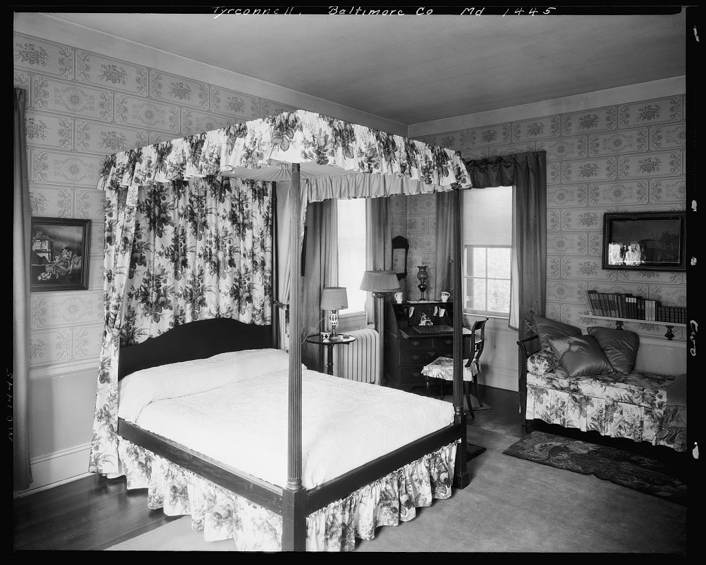 Antique canopy bed in wallpapered bedroom inside Baltimore's Tyrconnell House.