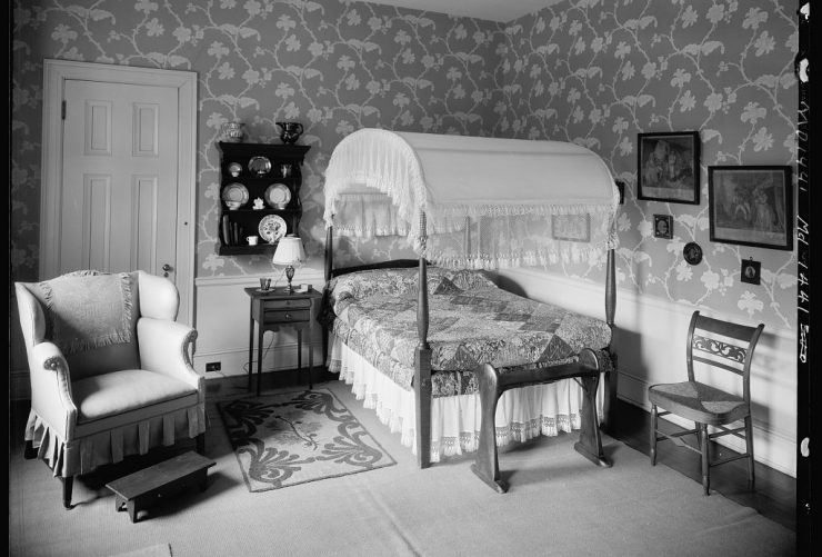 Antique filled bedroom with hand blocked wallpaper.